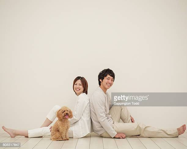 young couple with toy poodle sitting back to back - 背中合わせ ストックフォトと画像