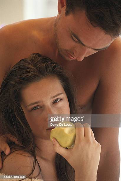 Young couple with woman holding apple