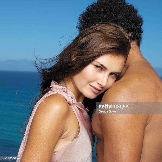 young couple with woman resting her head on man's chest close up