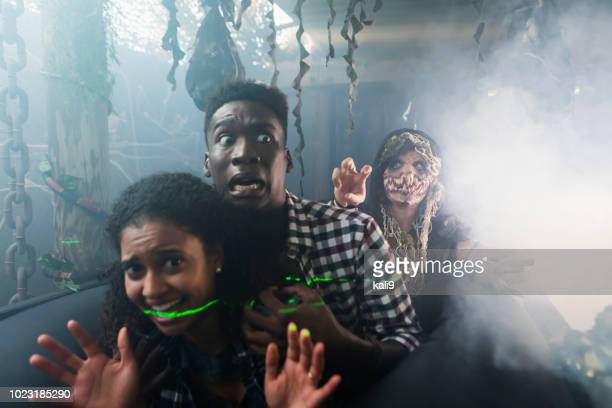 young couple with zombie in halloween haunted house - zombie face stock photos and pictures