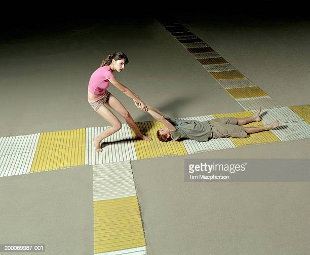 young couple, woman dragging man along slatted walkway on beach - dragging stock pictures, royalty-free photos & images