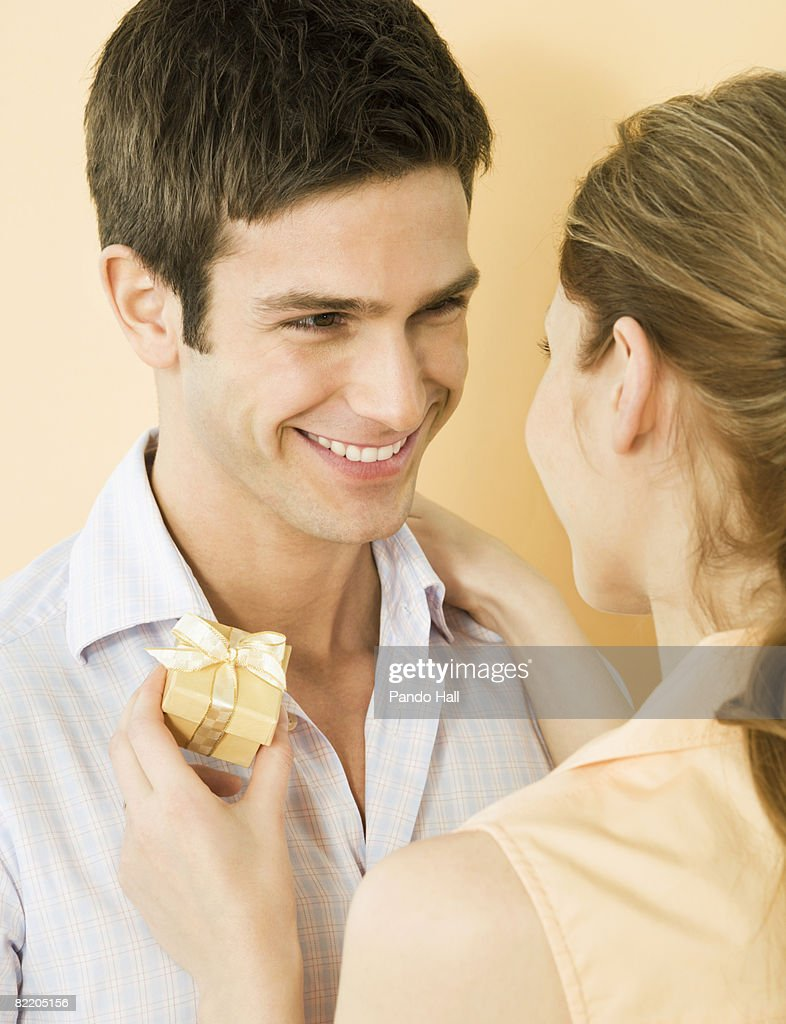 Young couple, woman holding gift, smiling : Stock Photo