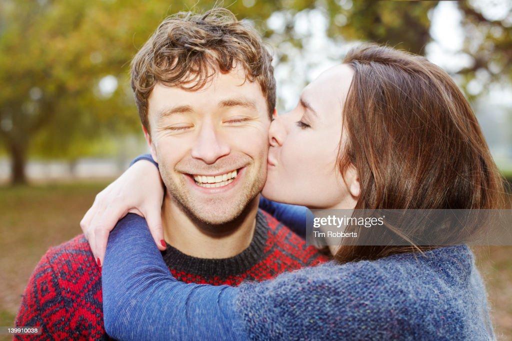 Young couple. Woman kissing man. : Stock Photo