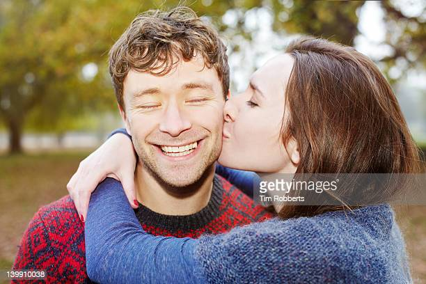 Young couple. Woman kissing man.