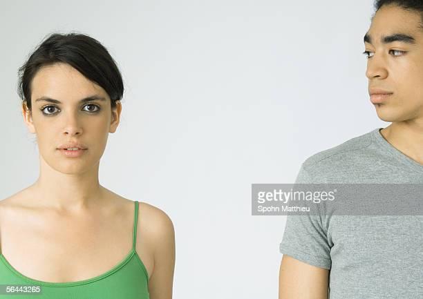 Young couple, woman looking at camera, man looking at woman