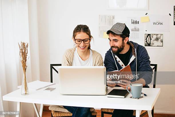 young couple working at modern home office - side by side stock photos and pictures