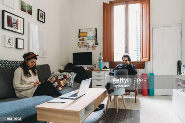 young couple working from home - aplanar a curva imagens e fotografias de stock