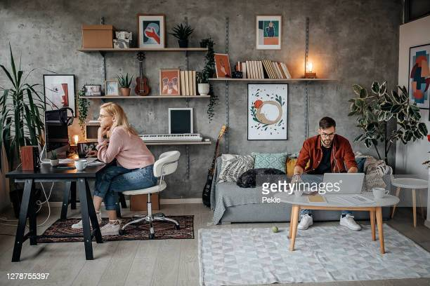 young couple working from their home office during pandemic - wife stock pictures, royalty-free photos & images