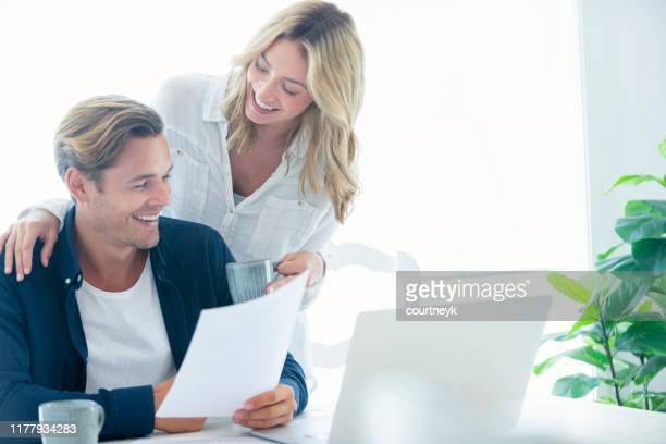 young couple working on their home finances and other paperwork. - bank statement stock pictures, royalty-free photos & images