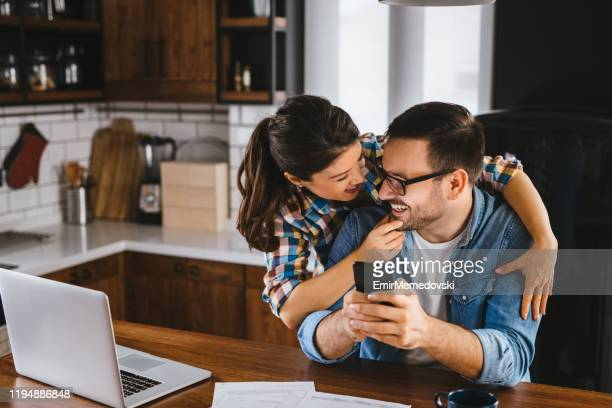 young couple working out family finances together at home using laptop - mortgage document stock pictures, royalty-free photos & images