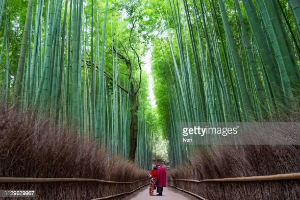young couple works in bamboo forest dressed in traditional kimono - präfektur okayama stock-fotos und bilder