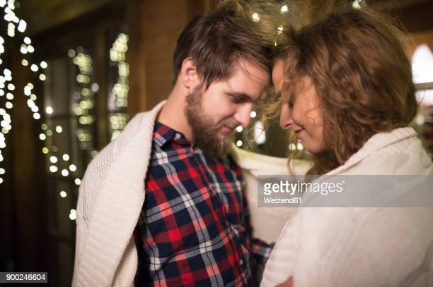 young couple wrapped in a blanket cuddling outdoors at night - hot couple photos et images de collection