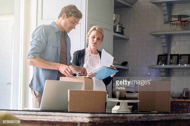 Young couple wrapping Christmas presents at home