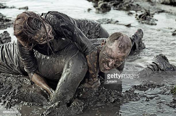 young couple wrestling during a mud run - mud wrestling stock photos and pictures