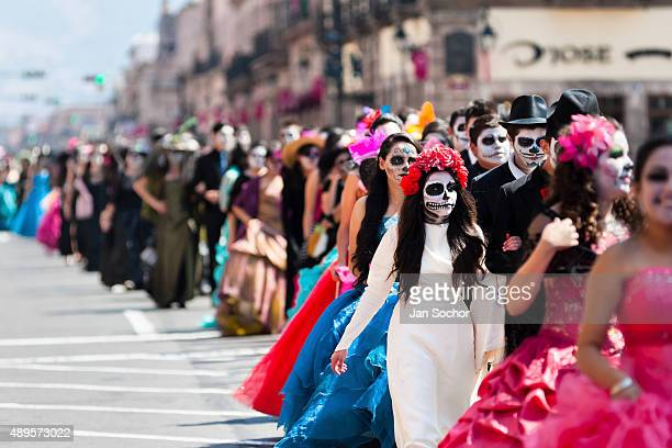 Young couples costumed as 'La Catrina' a Mexican pop culture icon representing the Death walk through the town during the Day of the Dead celebration...