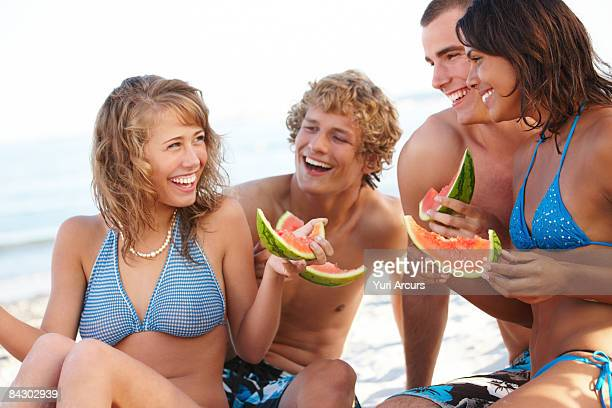 Young couples eating watermelon on beach