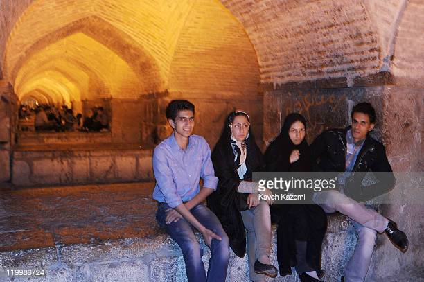 Young couples enjoy a cool spring evening sat under Khaju Bridge, arguably the finest bridge in the province of Isfahan, Iran. It was built by the...