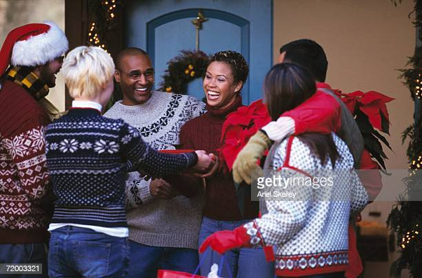 young couples greeting on porch at christmas time - arrival photos stock photos and pictures