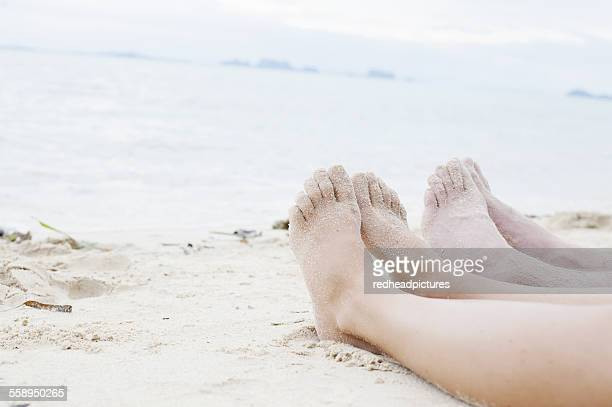 Young couples legs on beach, Kradan, Thailand