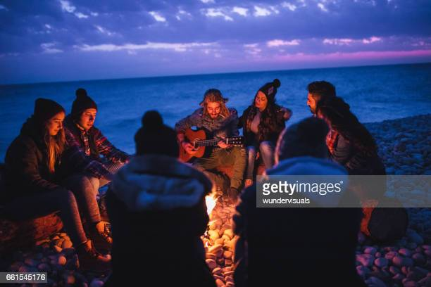 Young couples listening to music around campfire at the beach