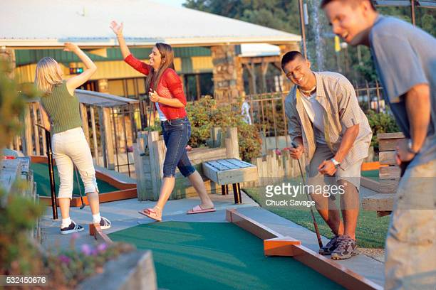 Young Couples Playing Miniature Golf