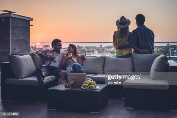 young couples relaxing on a penthouse patio at sunrise. - balcony stock pictures, royalty-free photos & images