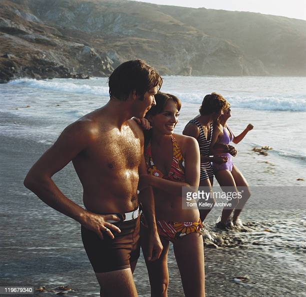 jeune couple debout sur la plage, souriant - film d'archive photos et images de collection