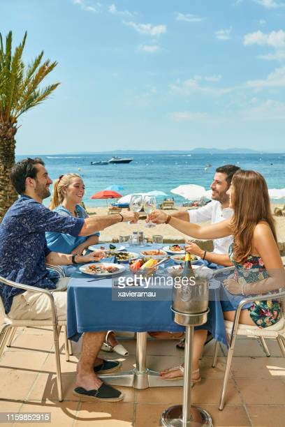 young couples toasting over lunch at sunny costa brava cafe - mediterranean culture stock pictures, royalty-free photos & images