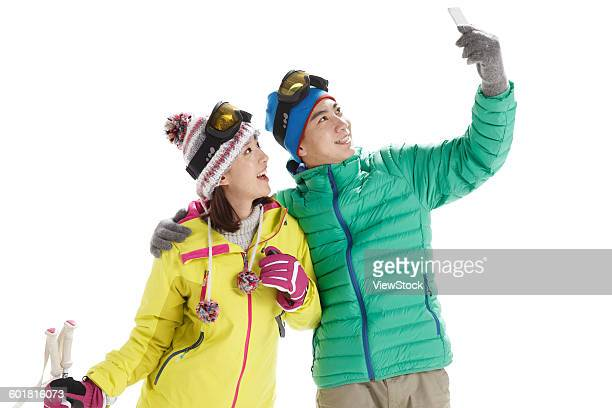 Young couples use mobile phones to take pictures