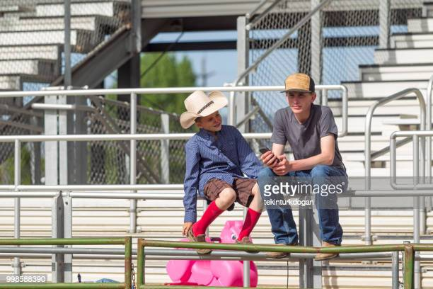 young cowboy big brother at rodeo