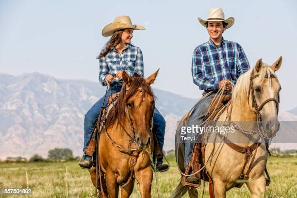 Young Cowboy and Cowgirl Having Fun While Riding Their Horses