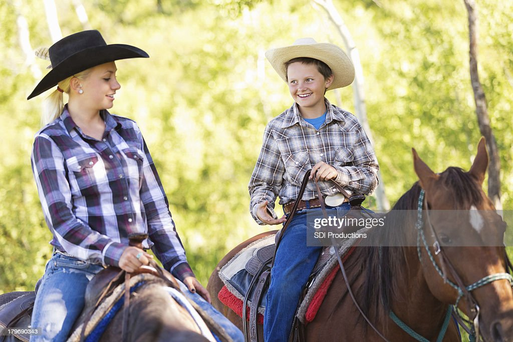 Young cowboy and cowgirl riding horses during trail ride : Stock Photo