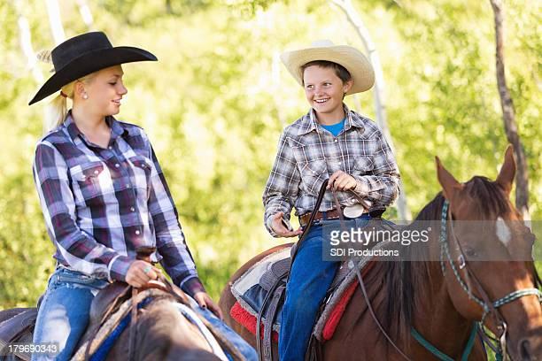 若いカウボーイと馬のカウガールの乗馬での乗馬