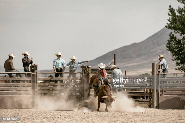 A young cowboy bareback riding on a bucking bull while a group of cowboys watch him in the background.