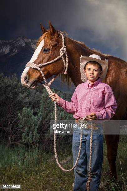 Young Cowboy Holding Horse's Head