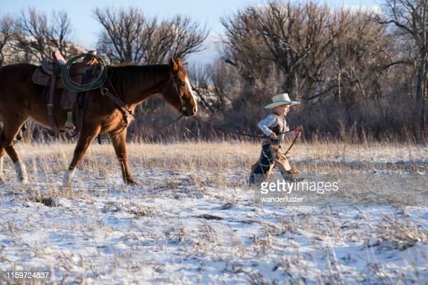 junger cowboy führt ein viertel pferd - anführen stock-fotos und bilder