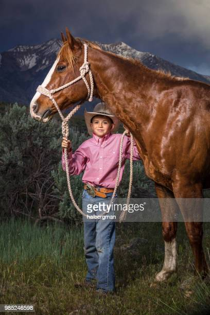 Young Cowboy Looking Under Horse's Head