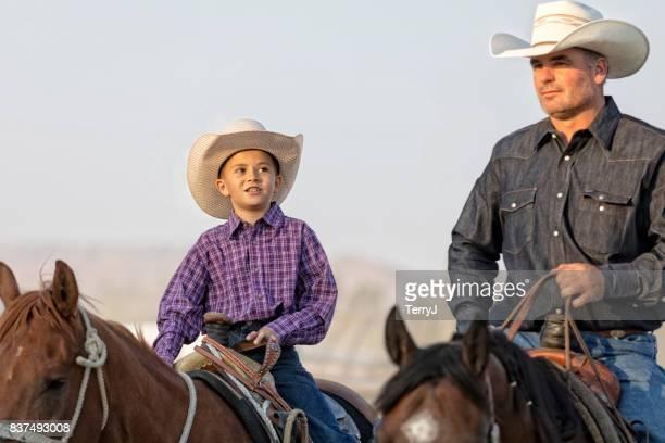 jovem vaqueiro parece up ao pai, ao montar um cavalo - cavalo família do cavalo - fotografias e filmes do acervo