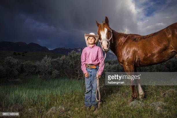 Young Cowboy Posing with Horse