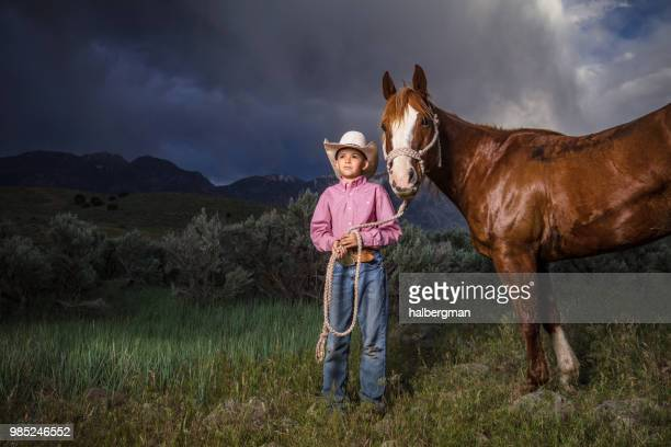 Young Cowboy Posing With Horse Under Stormy Sky