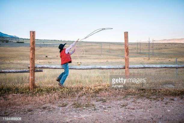 cowboy novo que pratica roping uma cerca de trilho - coluna de madeira - fotografias e filmes do acervo