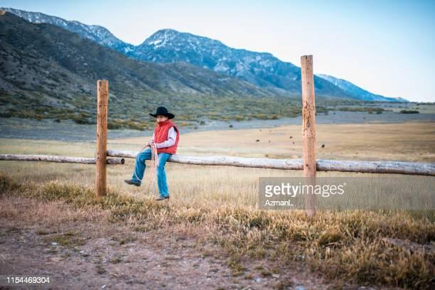 cowboy novo que senta-se na cerca de trilho com lasso - coluna de madeira - fotografias e filmes do acervo