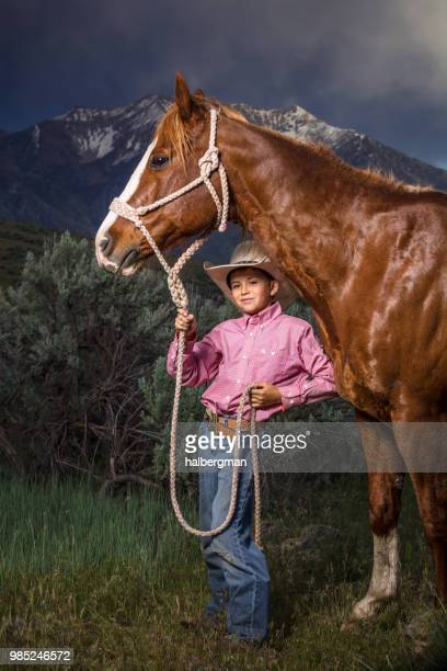 Young Cowboy Smiling at Camera from Under Horse's Head