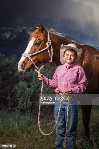 Young Cowboy Smiling Beside Horse