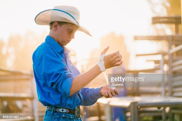 young cowboy wrapping his hands - bucking stock photos and pictures