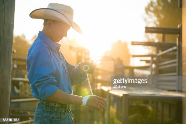 Young cowboy wrapping his hands ready to ride