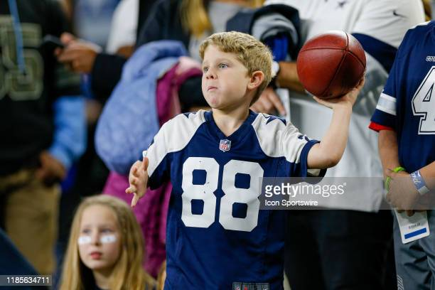 Young Cowboys fan plays catch with a coach on the sideline prior to the game between the Buffalo Bills and Dallas Cowboys on November 28, 2019 at...