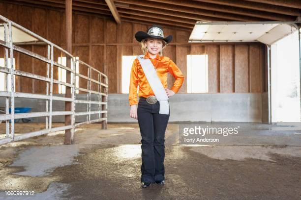 young cowgirl pageant contestant standing in barn - sjerp stockfoto's en -beelden