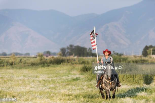 young cowgirl riding her horse while proudly holding the american flag in a utah field, with the wasatch mountains visible in the background. - flag bearer stock pictures, royalty-free photos & images