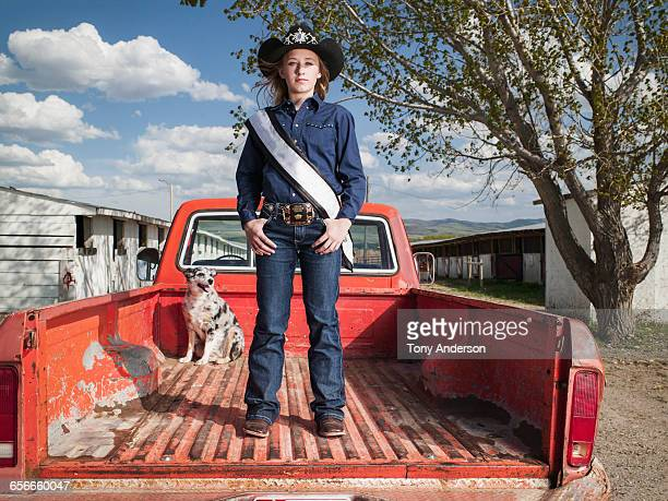 Young cowgirl standing in pickup truck with dog